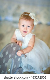 Image of sweet baby girl in a wreath, closeup portrait of cute 8 month-old smiling girl,  toddler