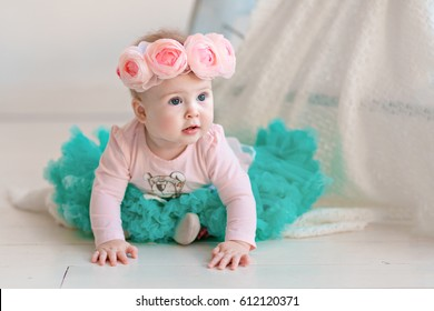 Image of sweet baby girl in a wreath of pink roses, closeup portrait of cute 8 month-old smiling girl,  toddler