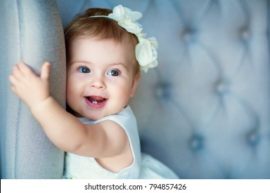 Image of sweet baby girl in a wreath, closeup portrait of cute 8 month-old smiling girl,  toddler.Studio shooting.