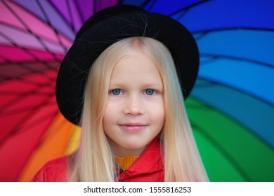 Image of sweet blond girl with long hair, closeup portrait of cute seven years old smiling girl with colorful umbrella. Outdoor autumn.