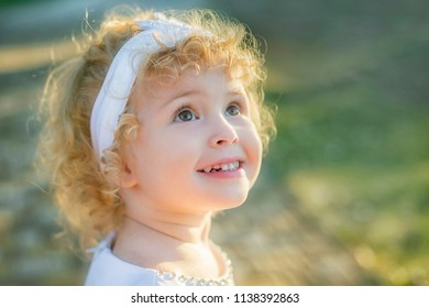 Image of  sweet and funny blond baby girl outdoor, cute toddler with amazed smiling face. Two years old.