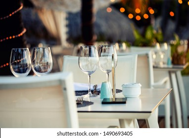 Image of table close-up in front of street restaurant with lights background