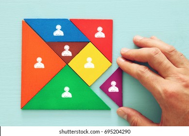 image of tangram  puzzle blocks with people icons over wooden table ,human resources and management concept.