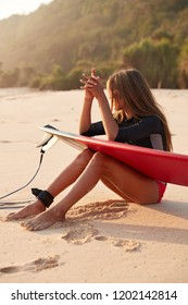 Image of tanned sporty healthy woman uses surfboard with leg leash, ready to surf on beach, keeps hands together, looks aside, breathes fresh marine air and admires beautiful scenery, enjoys lonliness