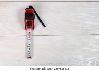 Image of tape measure  on white wooden background with copyspace.