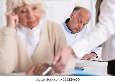 Image of teacher helping senior woman during exam