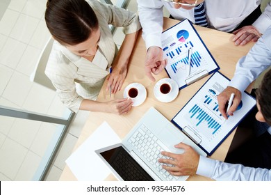Image of team during work with laptop and business documents at meeting