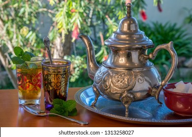 Image of teapot and Moroccan tea with a blurred garden background
