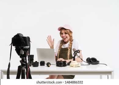 Image of teenage girl recording blog broadcast with microphone about new professional photocamera and technics isolated over white wall in studio