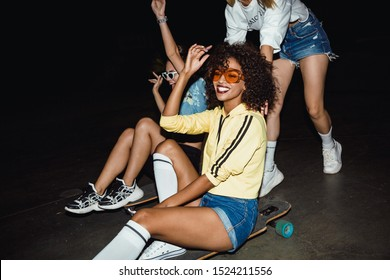 Image of teenage multinational girls in streetwear smiling and riding on skateboards at night party outdoors