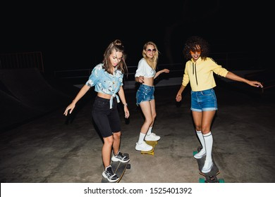 Image of teenage multinational girls in streetwear smiling and riding skateboards at night outdoors