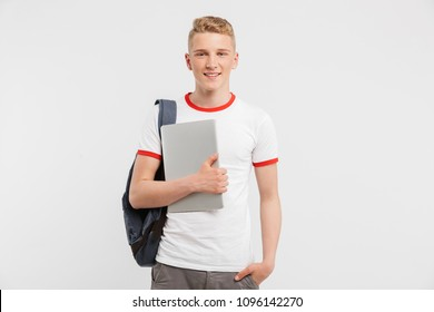 Image of teenager guy 16-18 years old wearing casual clothing and backpack looking at you with holding laptop in hand isolated over white background