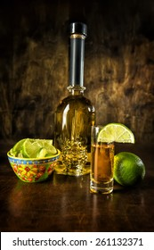 Image of a tequila bottle, shot with lime and lime wedge