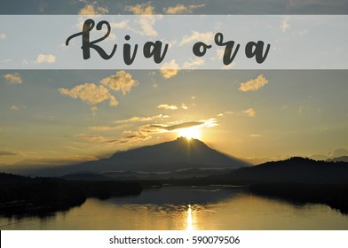 Image with the text KIA ORA, Maori word for good morning with beautiful sun rising grandly from behind a mountain. Concept idea for greeting, tourism, language teaching and for background purposes.