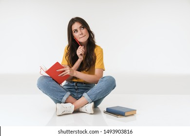 Image of thinking dreaming thoughtful young woman isolated over white wall background writing notes in notebook.