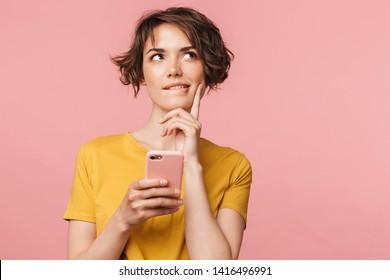 Bild einer träumenden jungen, schönen Frau, die sich einzeln auf rosafarbenem Wandhintergrund mit dem Handy stellt.