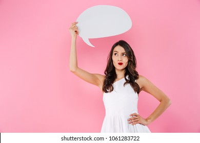 Image of thinking young asian woman standing isolated over pink wall background holding speech bubble.