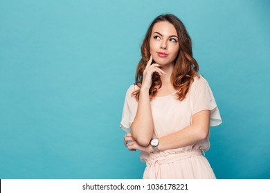 Image of thinking young lady standing isolated over blue background. Looking aside.
