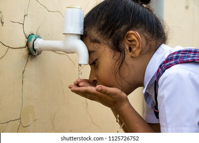 Image of a thirsty school girl drinking water from a tap