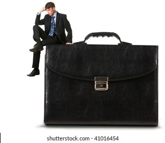 Image of thoughtful businessman sitting on briefcase