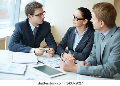 Image of three business people negotiating at meeting
