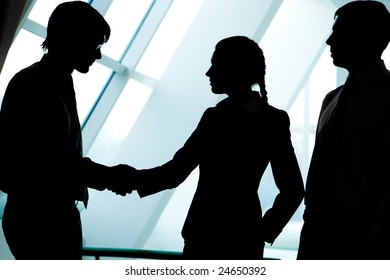 Image of three businesspeople figures with man and woman handshaking