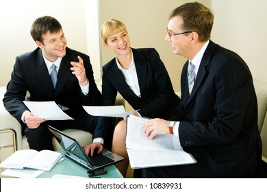 Image of three confident entrepreneurs discussing a new business decision