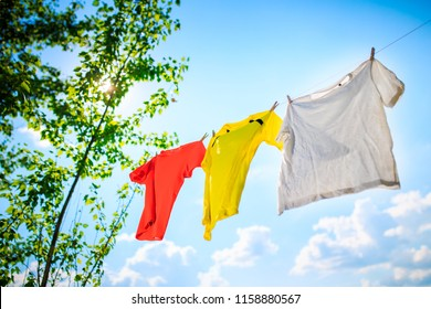 Image of three different colored T-shirts hanging on ropes against blue sky with tree tops.