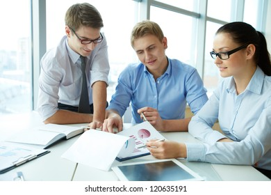 Image of three employees discussing papers at meeting