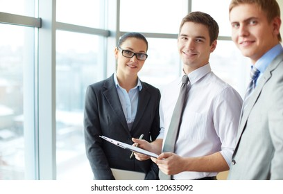 Image of three employees looking at camera, focus on elegant man with clipboard