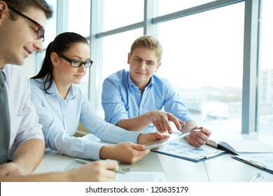 Image of three employees looking at touchscreen at meeting