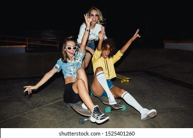 Image of three multinational girls in streetwear smiling and riding on skateboards at night party outdoors