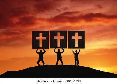 Image of three people lifting big boards with crucifix symbol while standing on the hill at sunrise