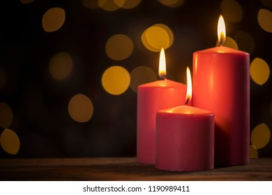 Image of three red candles on the table with Christmas lights blur background
