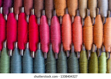 Image of three rows of colorful bobbin threads, stitching or sewing of red, orange, brown and other colors