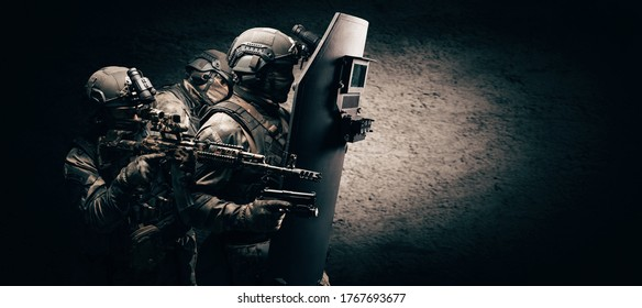 Image of three soldiers in a shooting computer game. ESports concept. They hide behind a tactical bulletproof shield. Mixed media