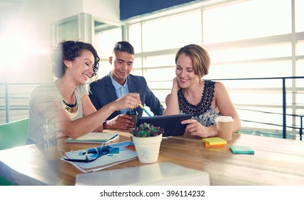 Image of three succesful business people using a tablet during at meeting