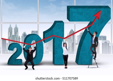 Image of three worker holding growth graph for year 2017 in the office
