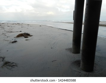 Image of tidal inlet water going under roadway bridge in the early morning. Bridge pilings are visible in image.