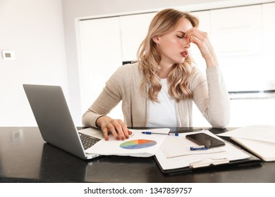 Image of a tired blonde woman posing sitting indoors at home using laptop computer work with documents.