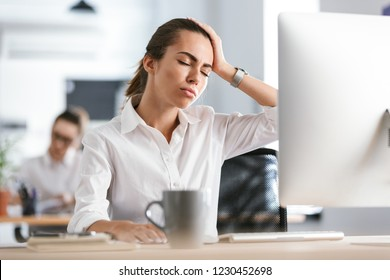 Image of a tired confused bored young business woman with headache work in the office with computer.