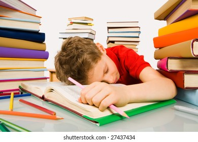 Image of tired schoolboy sleeping on pages of textbook with pink pencil in hand