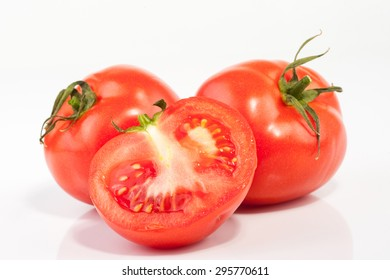 an image of Tomatoes. Whole and a half isolated on white