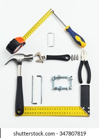 Image of tools in shape of house over white background. Home improving, repair concept