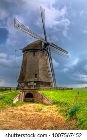 Image of a traditional Dutch windmill located in a green field during a cloudy day.