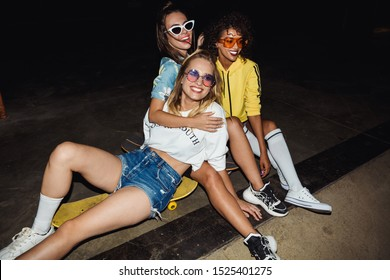 Image of trendy multinational girls in streetwear smiling and sitting on skateboards at night party outdoors