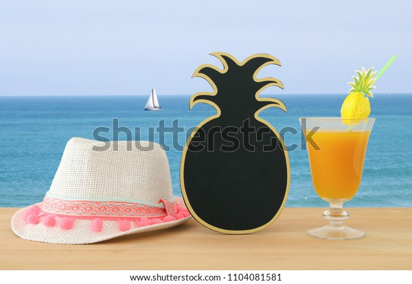 image of tropical and exotic fruit coctail, blank pineapple blackboard for copy space next to white fedora hat over wooden table