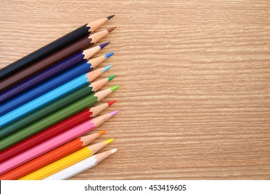 image of twelve color pencils on wooden background