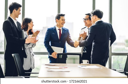 Image two asian business partners in elegant suit successful handshake together in front of group of casual business clapping hands in modern office.Partnership approval and thanks gesture concept