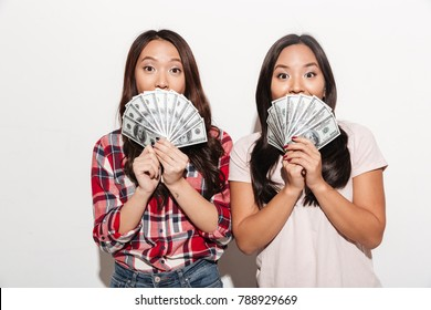 Image of two asian pretty cute ladies sisters standing isolated over white background. Looking camera covering faces with money.